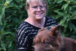 Na zdjęciu, na tle zieleni, Małgorzata w kolorowych okularach i bluzce z połyskującymi napisami. Klęczy obok psa rasy owczarek niemiecki i głaszcze go pod szyją.