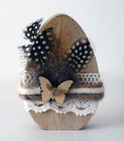 Zdjęcie przedstawia przestrzenny owalny przedmiot przypominający pisankę. Drewniane jajko owinięte jest w połowie koronkami i kolorową włóczką, która utrzymuje czarne nakrapiane piórka. Na środku pisanki przymocowany jest, za pomocą zwykłego sznurka, niewielki drewniany motyl.