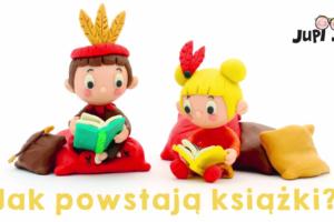 Na kolorowych poduszkach siedzą dwie postaci wykonane z plasteliny: chłopiec i dziewczynka. Chłopiec ma brązowe włosy oraz czerwoną czapkę z trzema żółtymi piórami, dziewczynka ma żółtw włosy związane w kucyki z przyczepionymi czerwonymi piórami. Z uśmiechem na ustach czytają książki. Pod nimi znajduje się napis jak powstają książki?