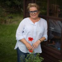 Pisarka Małgorzata Kalicińska w białej koszuli i w dżinsach opiera się o okno altany. W tle zieleń ogrodu.